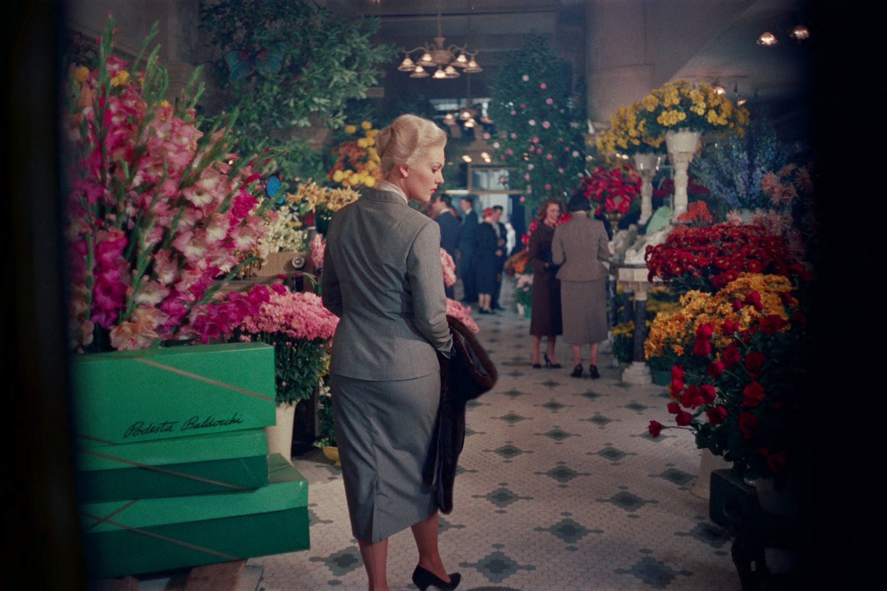 Woman in skirt suit walking through a flower shop