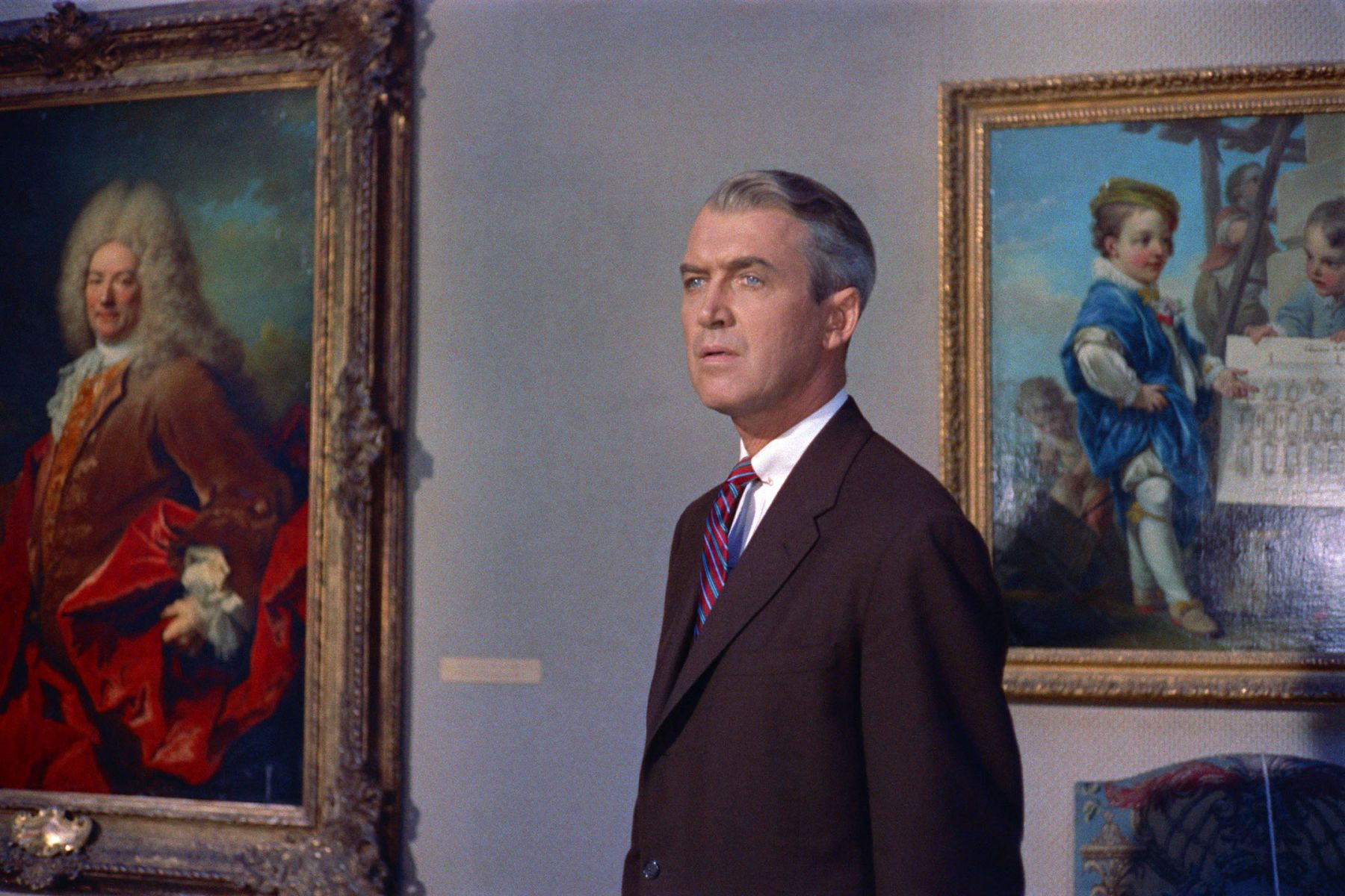 man in a suit stands before two classical paintings