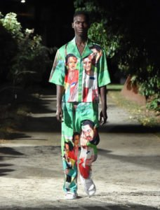 Pyer Moss Runway Model Wearing a green top and bottom printed with African faces of a boy and a man