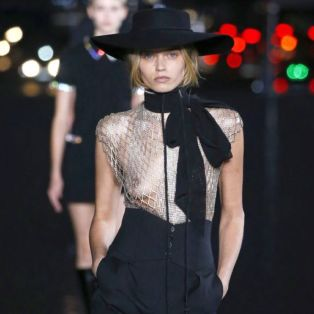 sexiest-womenswear designer of the year-YSL-2019-photo of runway model wearing hat, see through top, high waisted pants, long bow and lizard skin boots