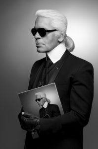 Karl Lagerfeld Holding a Magazine that shows Karl Largerfeld wearing the same outfit he is wearing