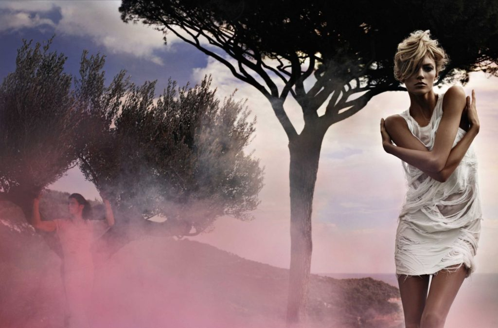 Karl-Lagerfeld_FENDI-Beautiful Blonde Model with arms crossed against a backdrop with image of trees and pink smoke haze