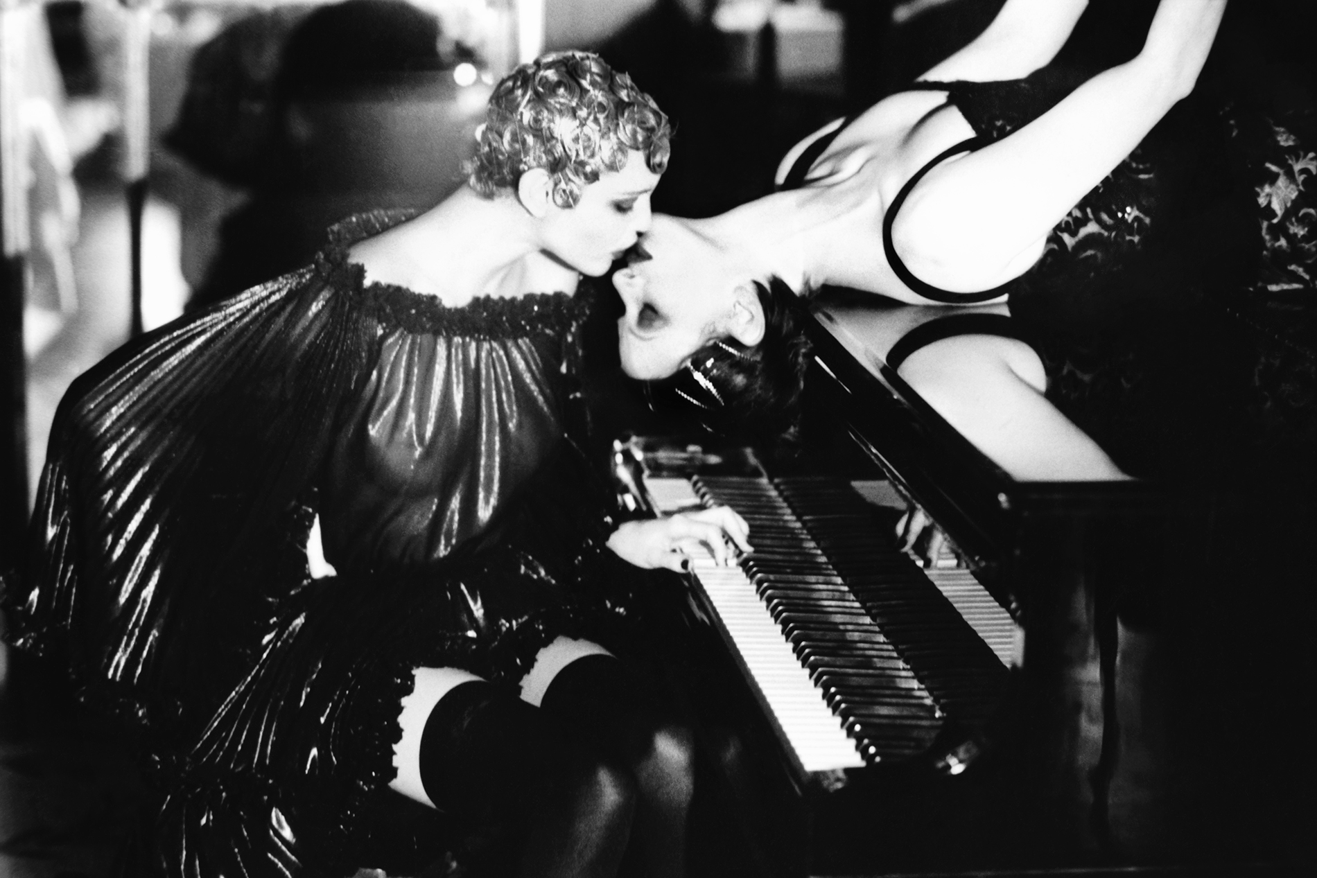 two women kissing on a grand piano