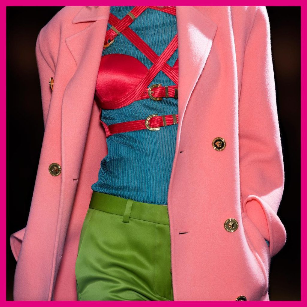 Versace Fall 2019 Runway Look-Pink Jacket with gold buttons, Pink Bondage Bra, Blue Sweater and Lime Green Pants