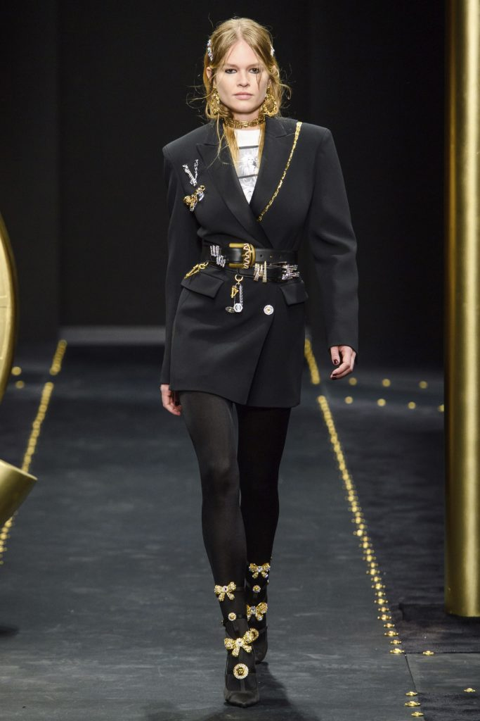 Versace Fall 2019 Runway Show-Model Wearing Black Blazer, Large gold earings, necklace and boots with gold bows
