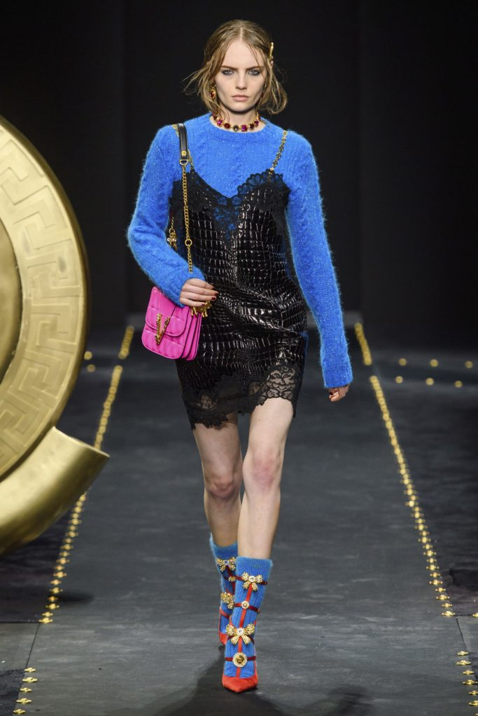 Versace Fall 2019 Runway Show-Model wearing black leather and lace tunic with gold staps, blue sweater and red shoes with blue socks