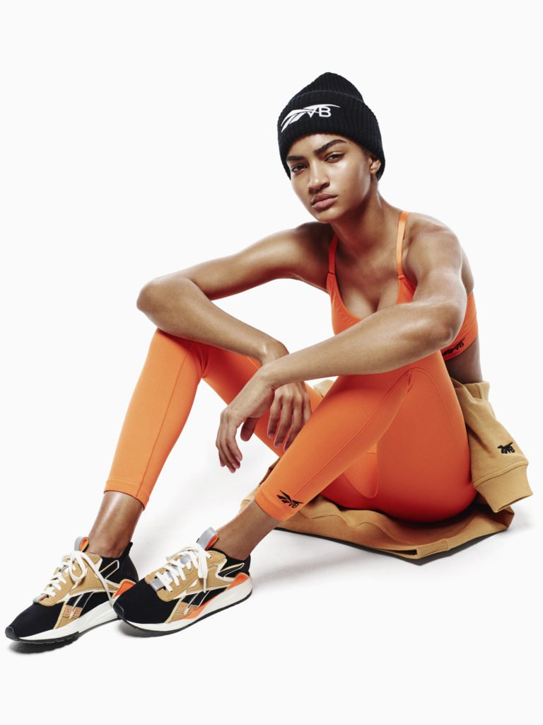 Victoria Beckman-Reebok Collection SS 2019 Campaign Photograph of Female Model in Hat, Orange Jog Bra, Sweatpants and Running Sneakers