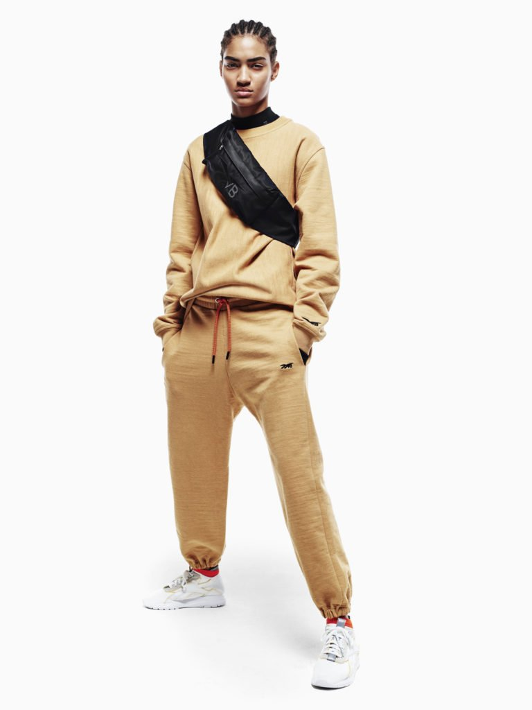 Victoria Beckman-Reebok Collection SS 2019 Campaign Photograph of Model wearing orange sweatshirt with black cross body pouch, orange sweatpants and white sneakers